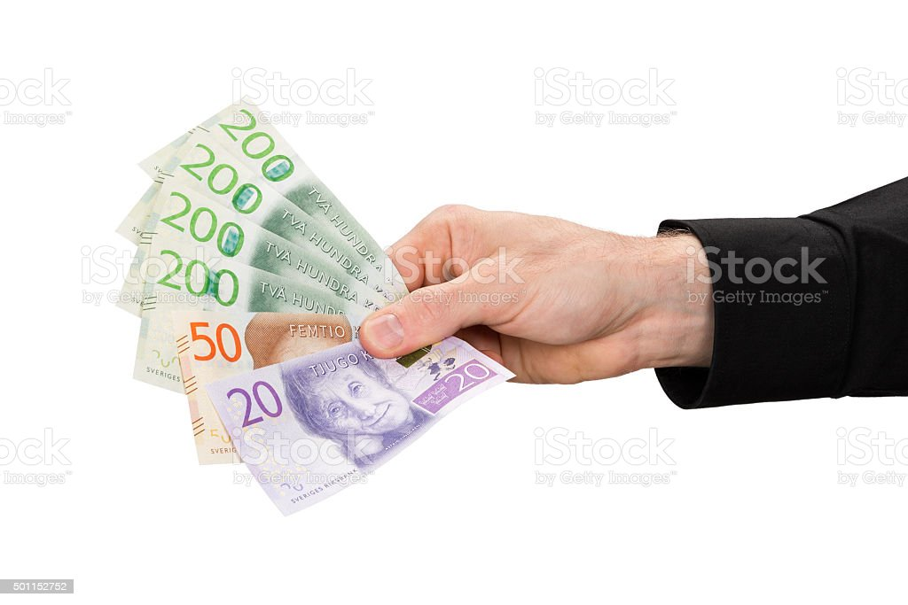 Man is holding swedish banknotes in his hand. stock photo