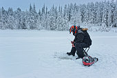 Man is ice-fishing in Ruka in Lapland in winter