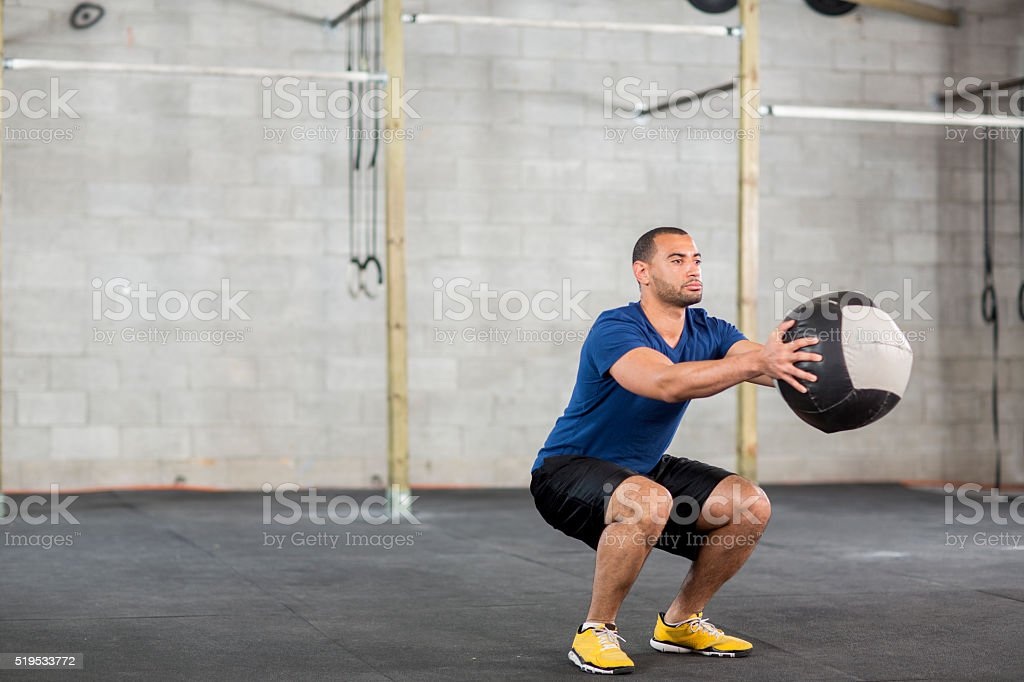 A man is lifting a weighted ball at the gym and is stock photo