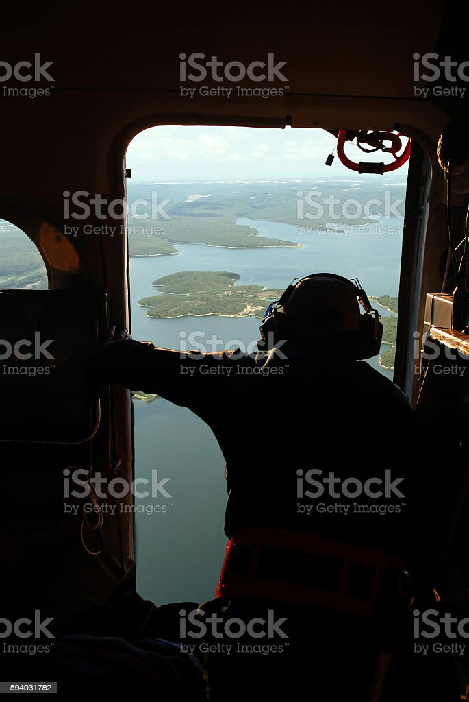 Man is looking at fire from in helicopter stock photo