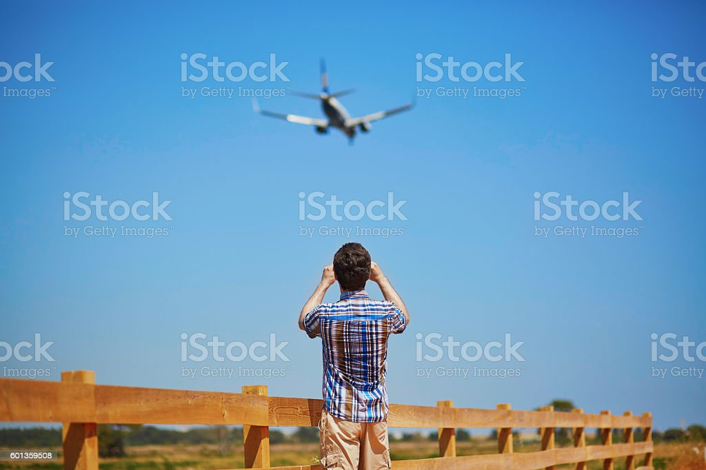 Man is looking at the glide path and landing plane stock photo
