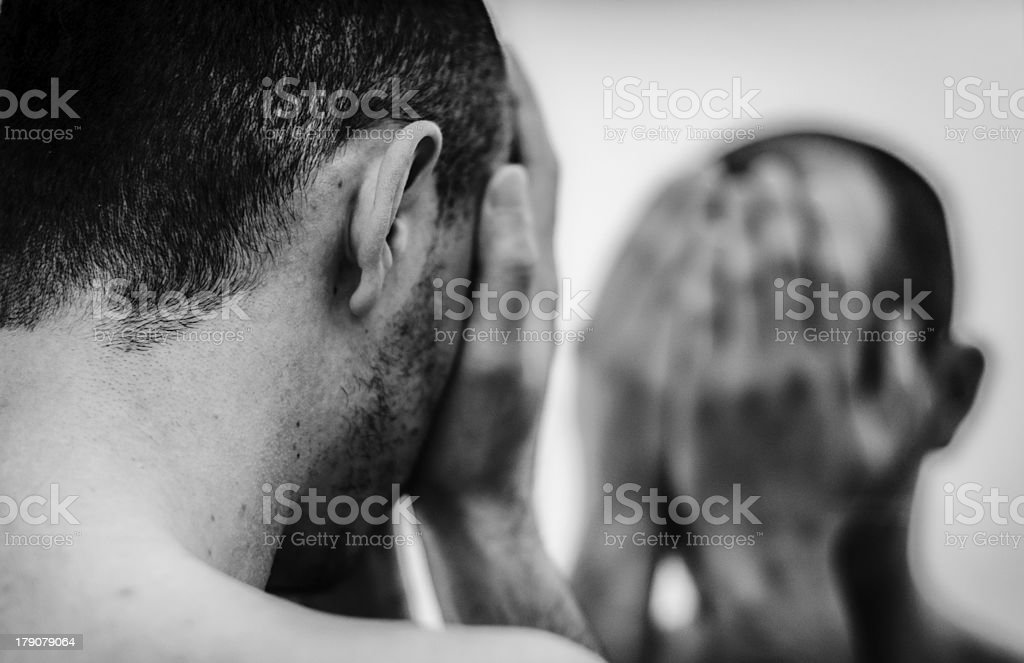 A man is looking into the mirror and covering his face  stock photo