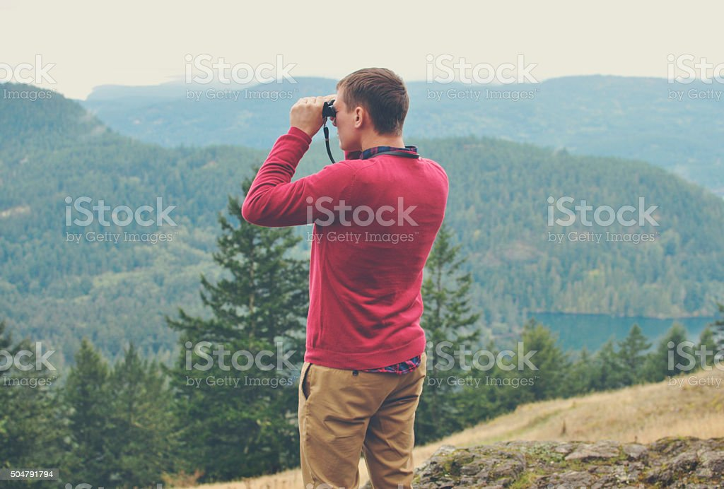 Man is looking through binoculars at a beautiful view stock photo
