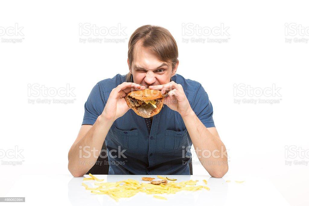 man is not careful eating tasteless burger stock photo