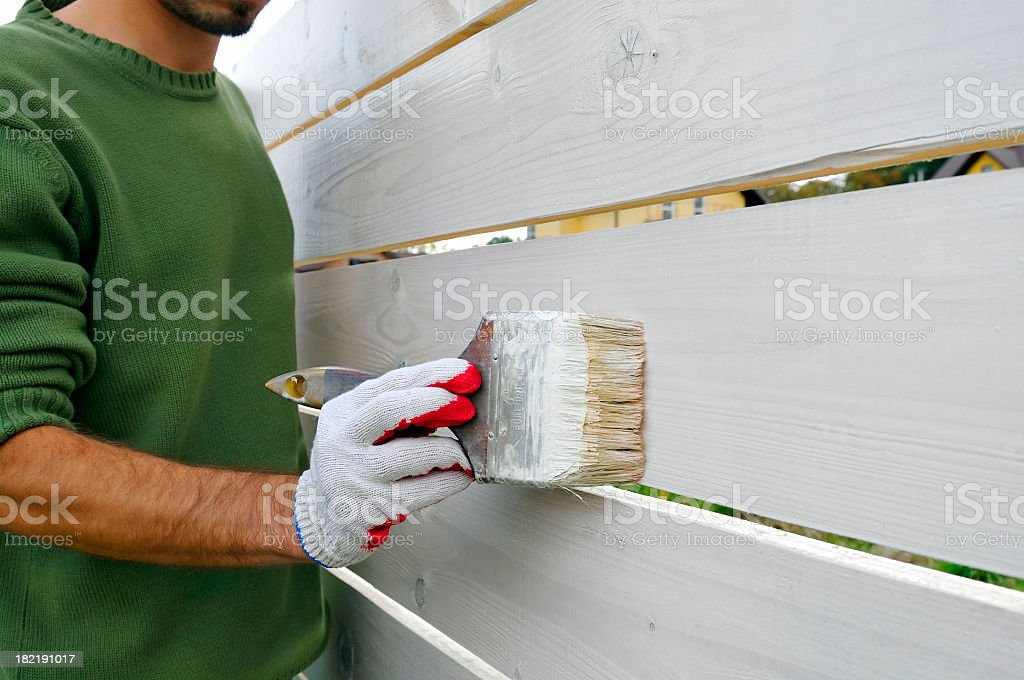 Man is painting with brush wooden fence on white color stock photo