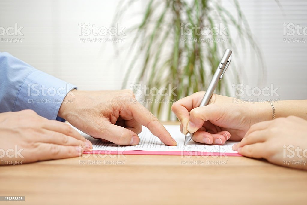 man is pointing  place where she should sign the agreement stock photo