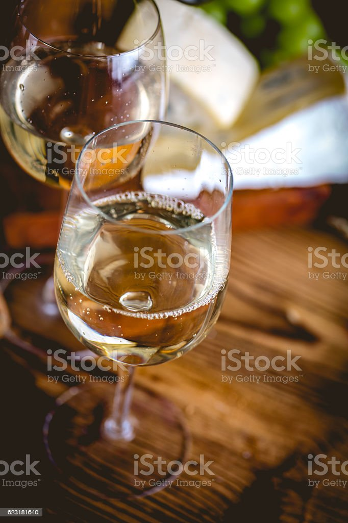 Man is pouring white wine into the glasses stock photo