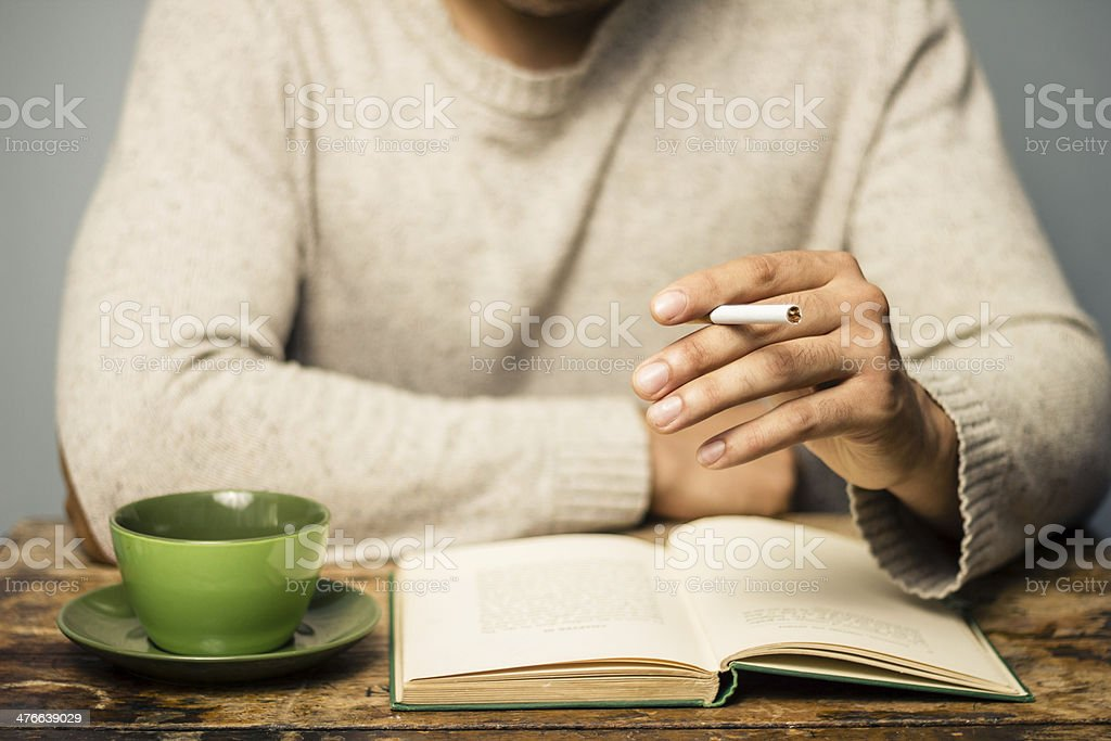 Man is reading and smoking in cafe stock photo
