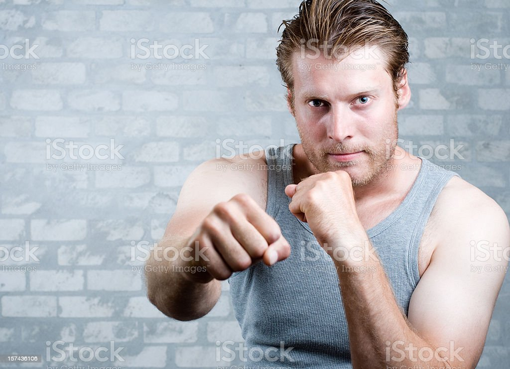 Man is ready to fight and throws a punch royalty-free stock photo