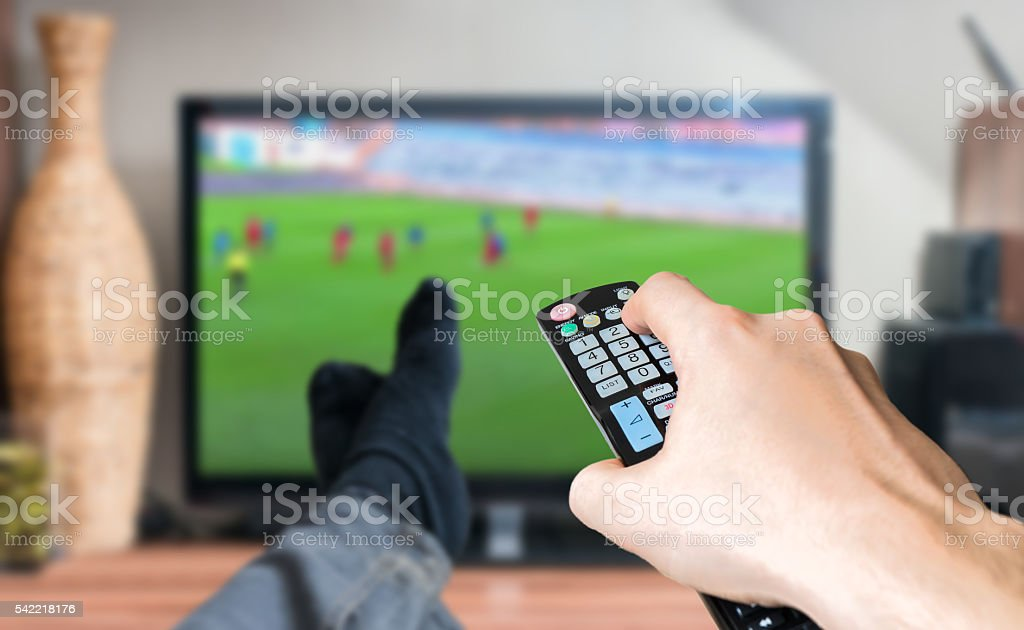 Man is relaxing and is watching football match on TV. stock photo
