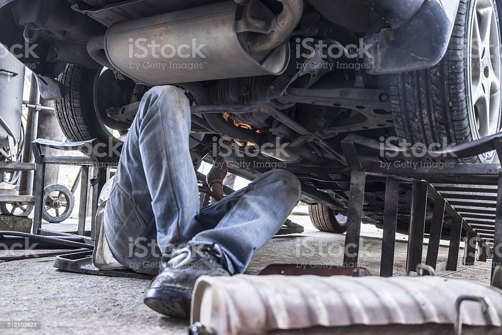 man is Reparing car by welding stock photo