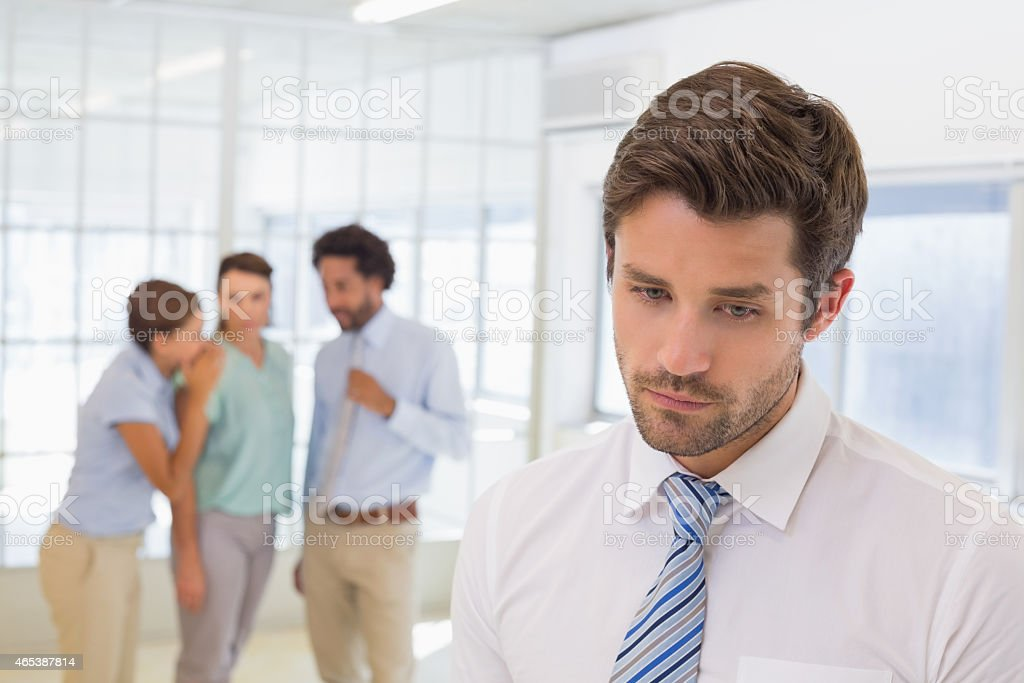 Man is sad because his colleagues are gossiping about him stock photo