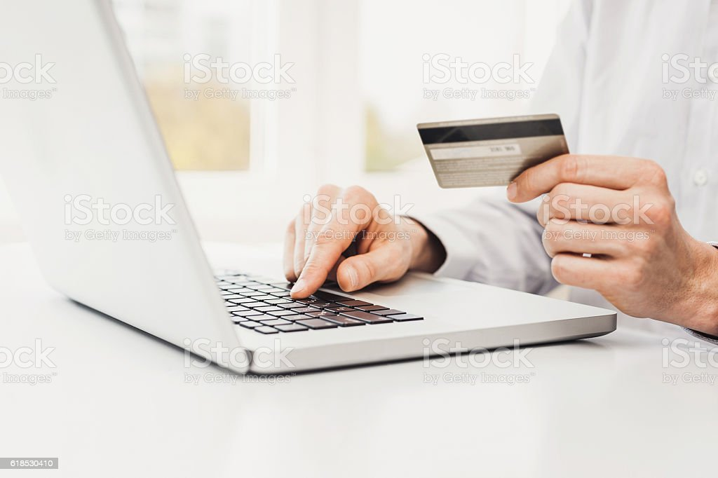 Man is shopping online with laptop stock photo