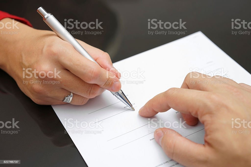 Man is showing woman where to sign stock photo