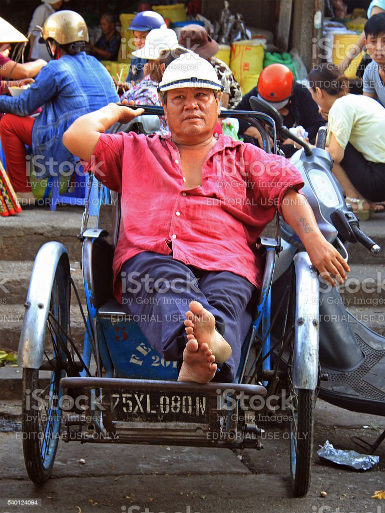 man is sitting in a cart on street market stock photo