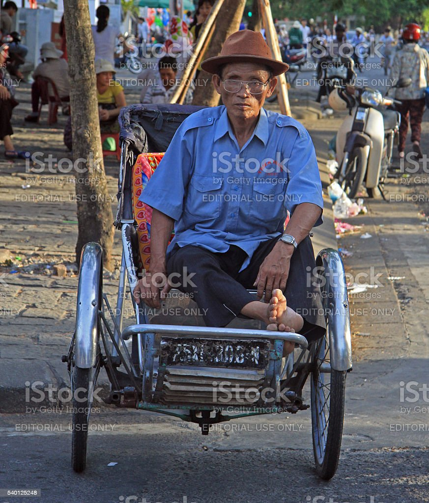 man is sitting in a cart on street stock photo