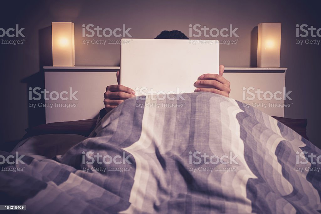 Man is sitting in bed behind his laptop royalty-free stock photo