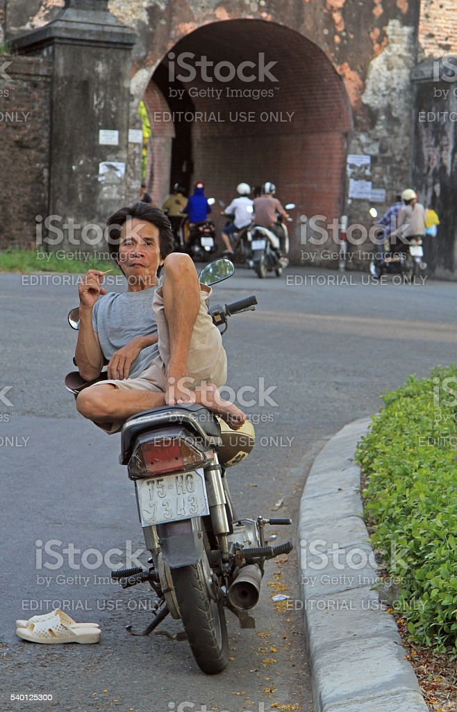 man is sitting on a scooter outdoor in Hue, Vietnam stock photo