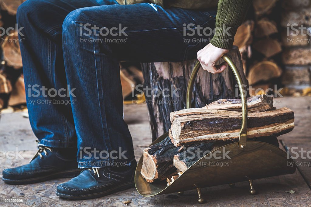 man is sitting on stump and holds woodpile firewood stock photo