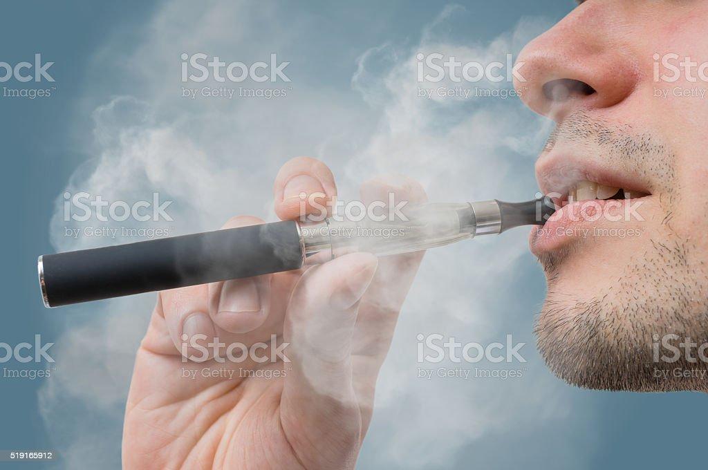 Man is smoking e-cigarette. stock photo