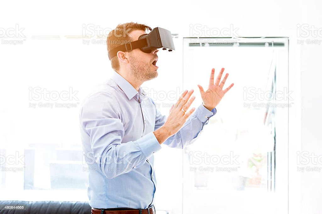 Man is surprised while using a virtual reality headet stock photo