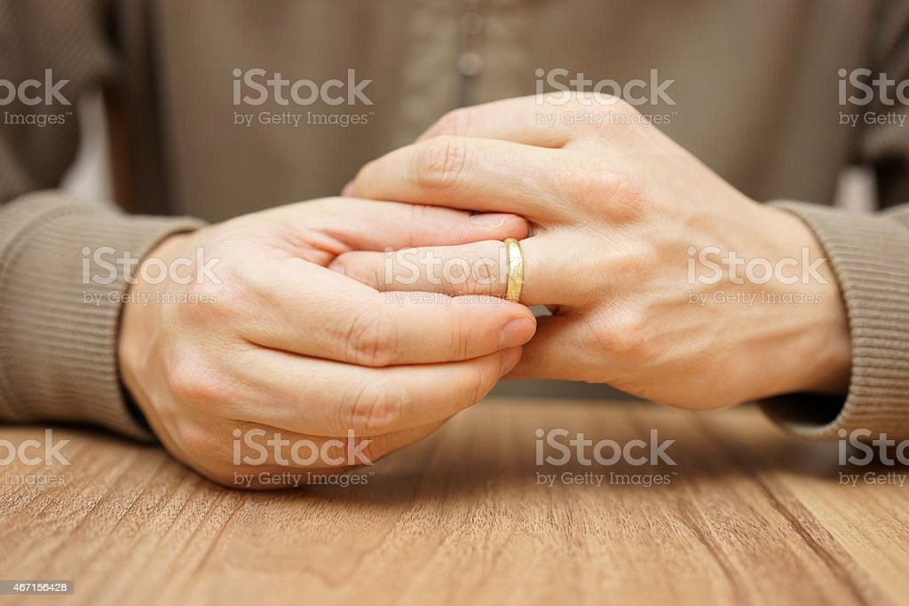 Man is taking off the wedding ring stock photo