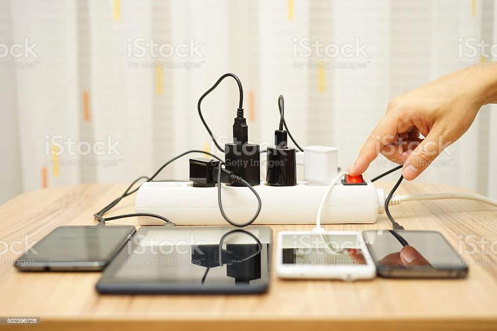 man is turning off  power adapters for mobile phones stock photo
