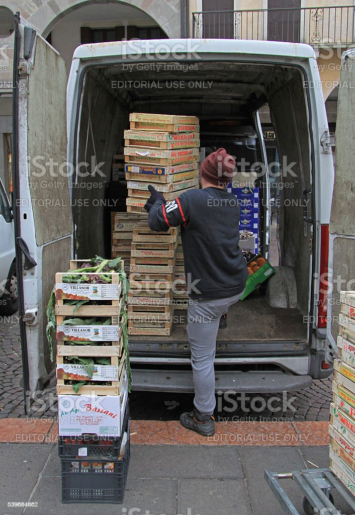 man is unloading boxes with fruits in Padua, Italy stock photo