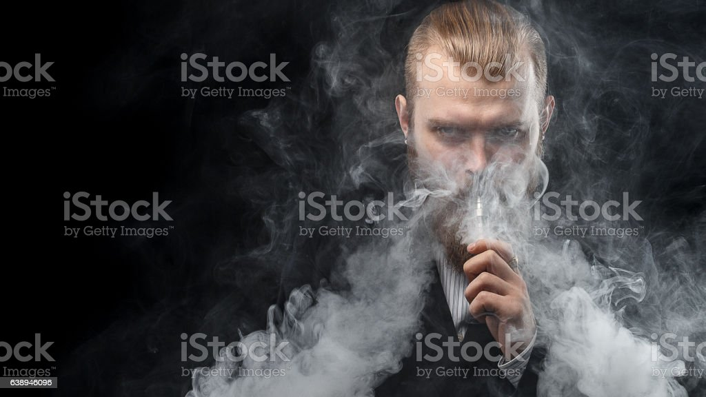 Man is vaping and holding e-liquid. Black background. stock photo