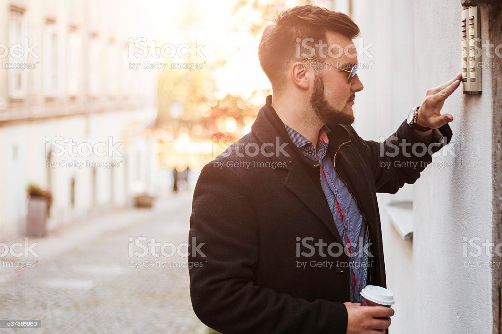Man is visiting his firend, rings doorbell stock photo