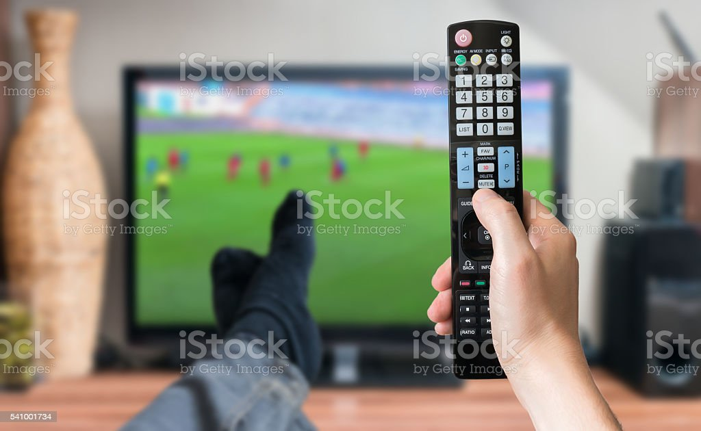Man is watching football match on tv with remote controller. stock photo