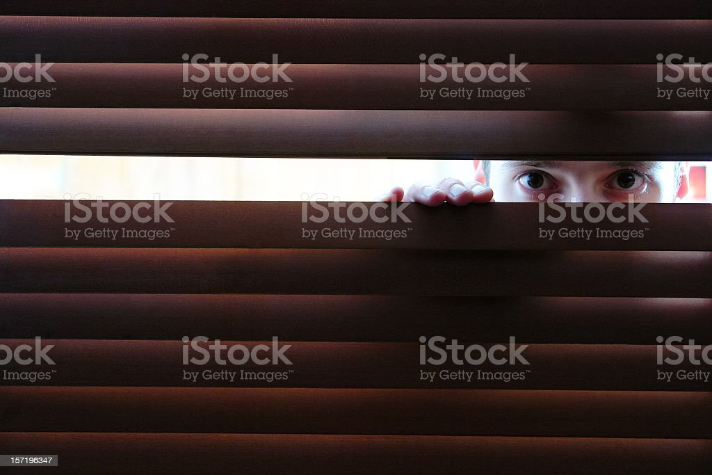Man is watching through hole in window's wooden blinds stock photo