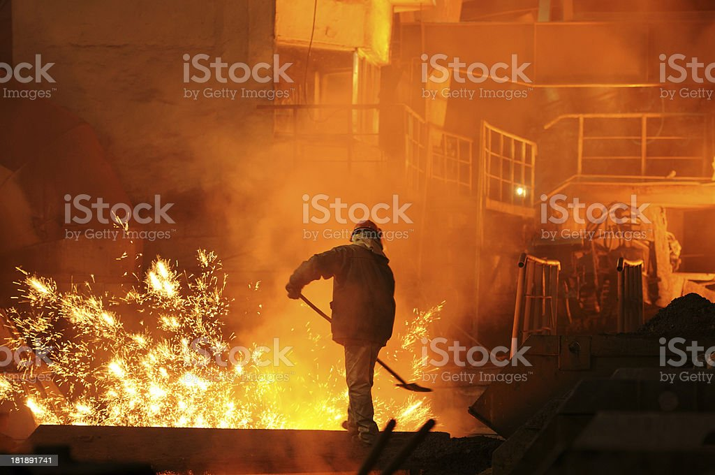 Man is working in the splashing molten iron stock photo