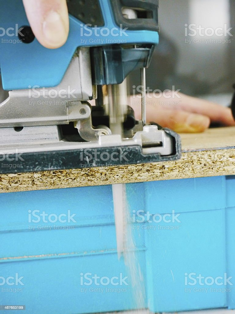 Man is working with electric jig saw stock photo