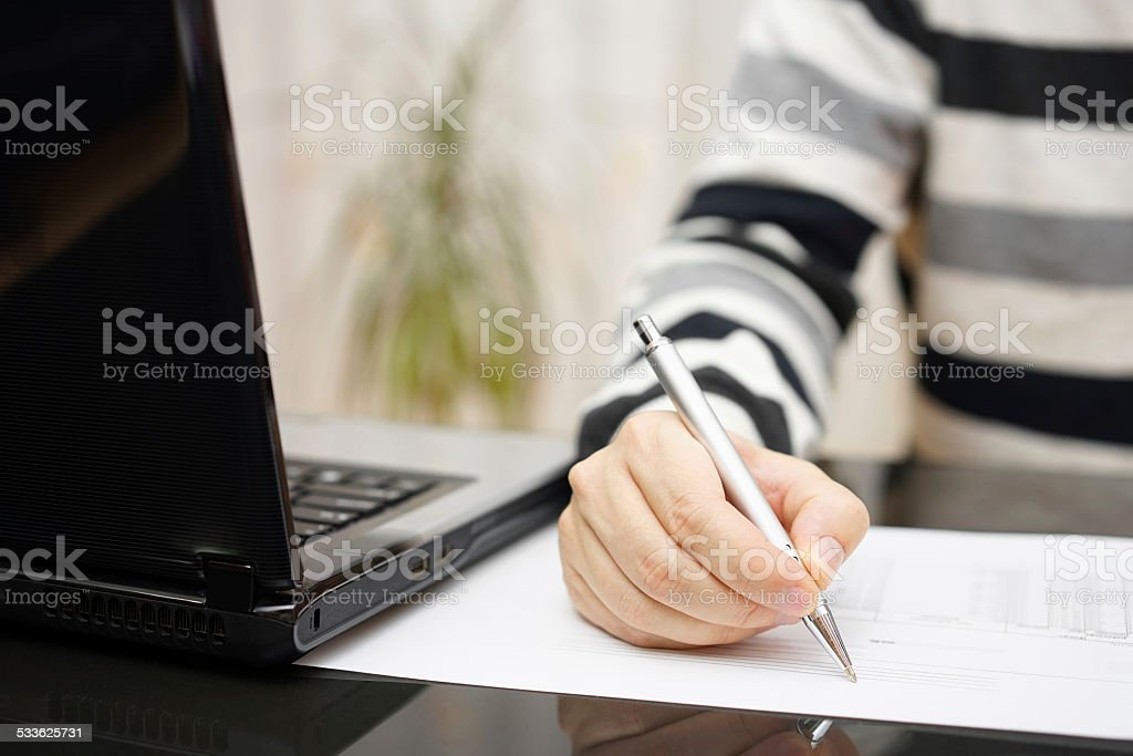 Man is writing document or studying with a laptop stock photo