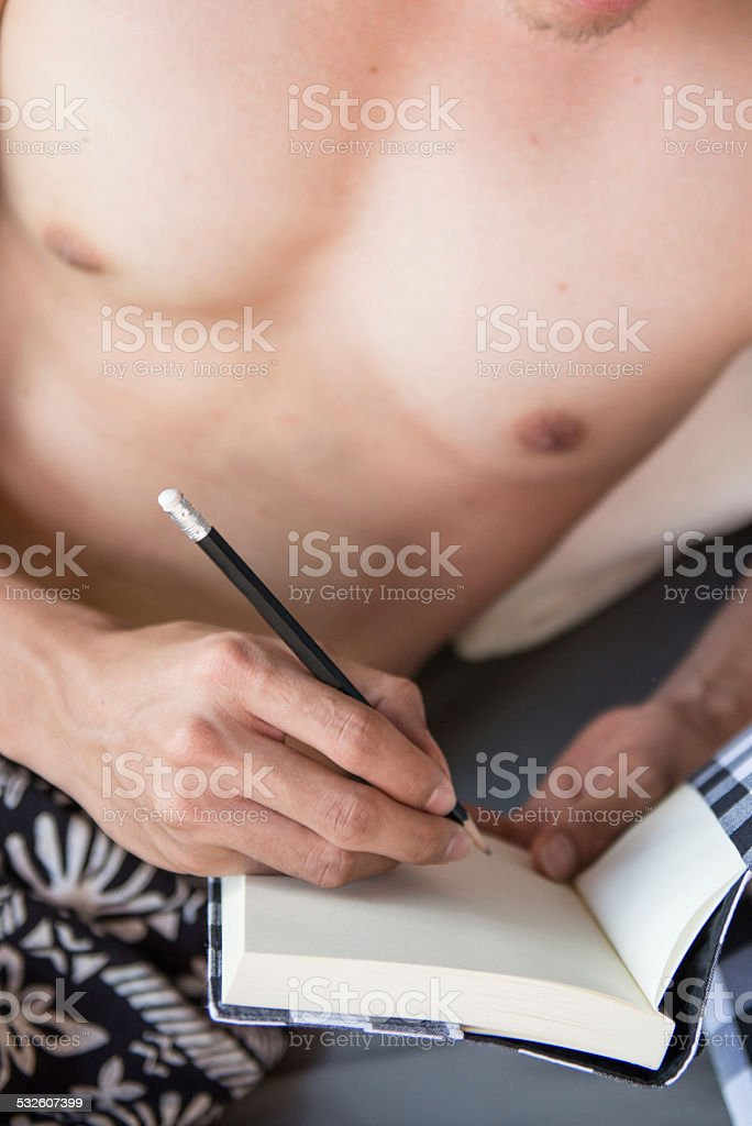 man is writing on the notebook in his hand stock photo