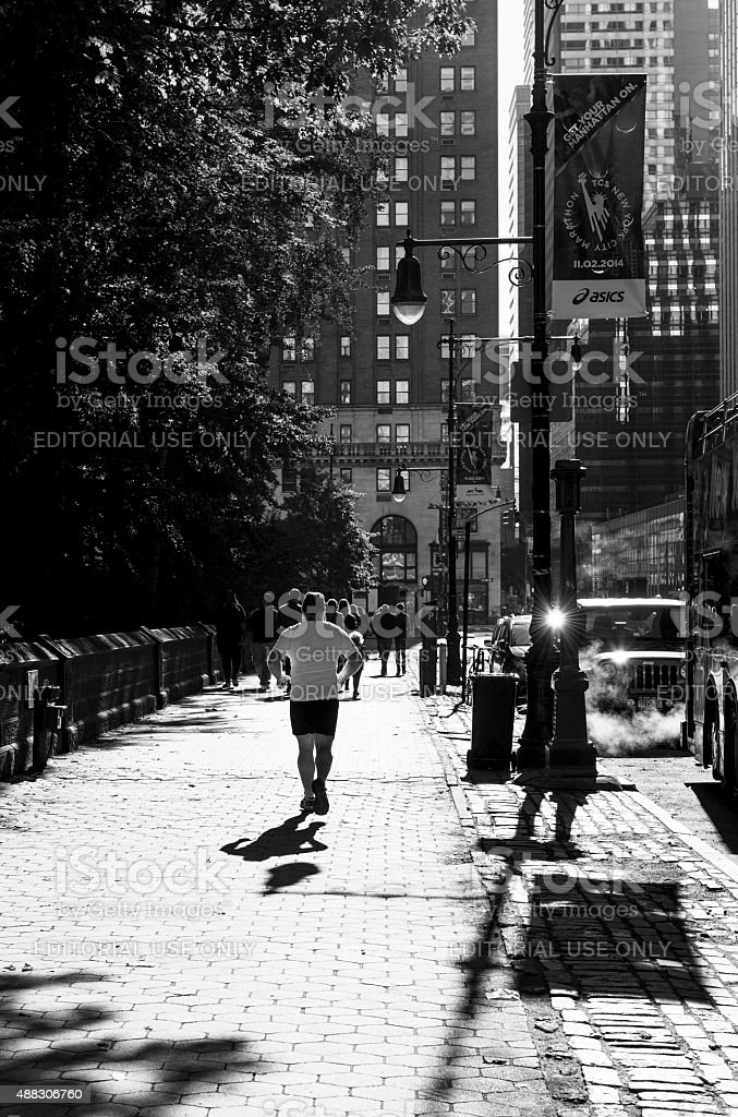 Man jogging at Central Park South in New York City stock photo