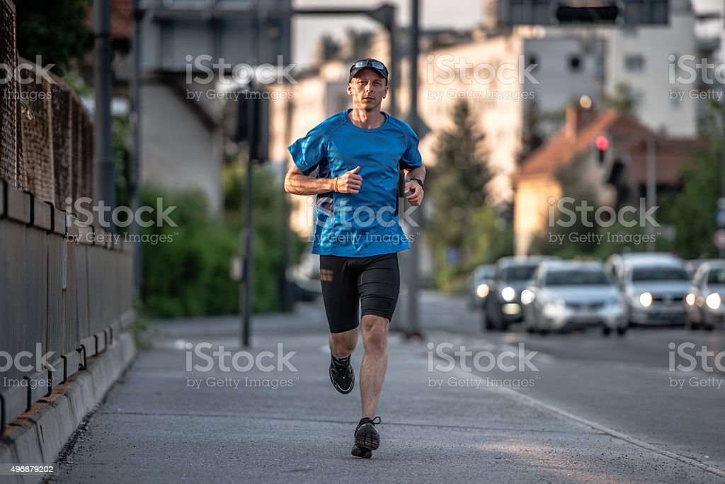 Man jogging in urban setting stock photo