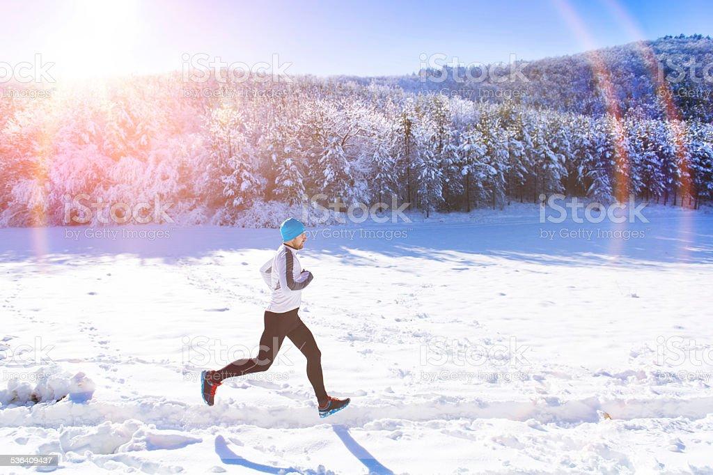 Man jogging in winter nature stock photo
