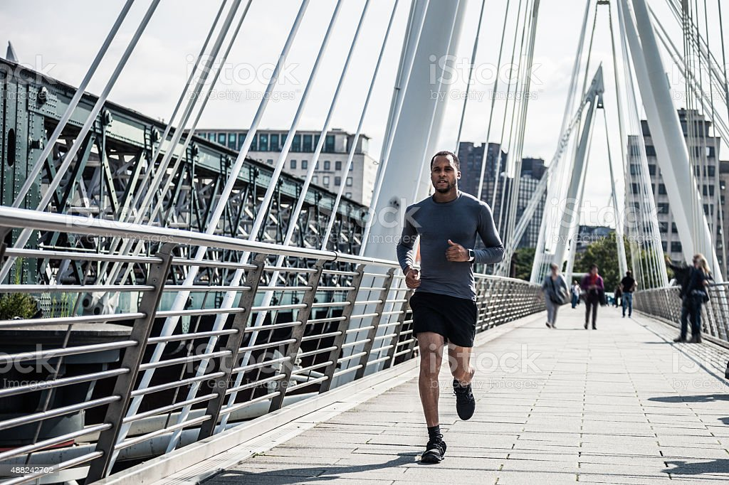 Man jogging on a modern bridge stock photo