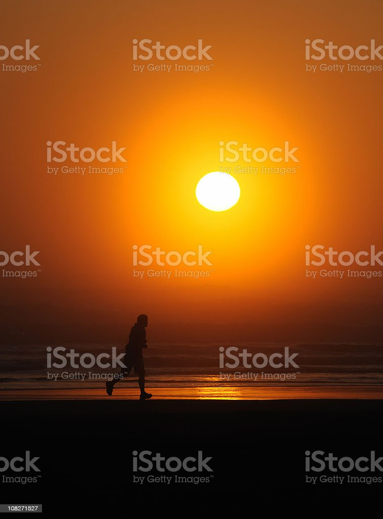 Man Jogging on Beach By The Setting Sun royalty-free stock photo