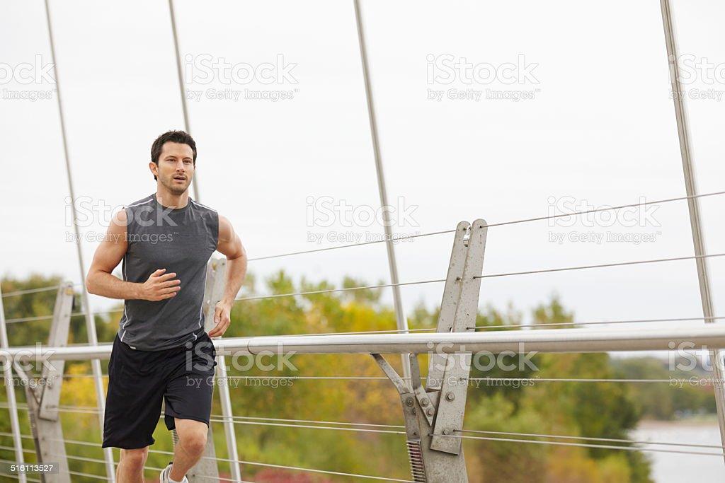 Man jogging on the bridge in the city stock photo