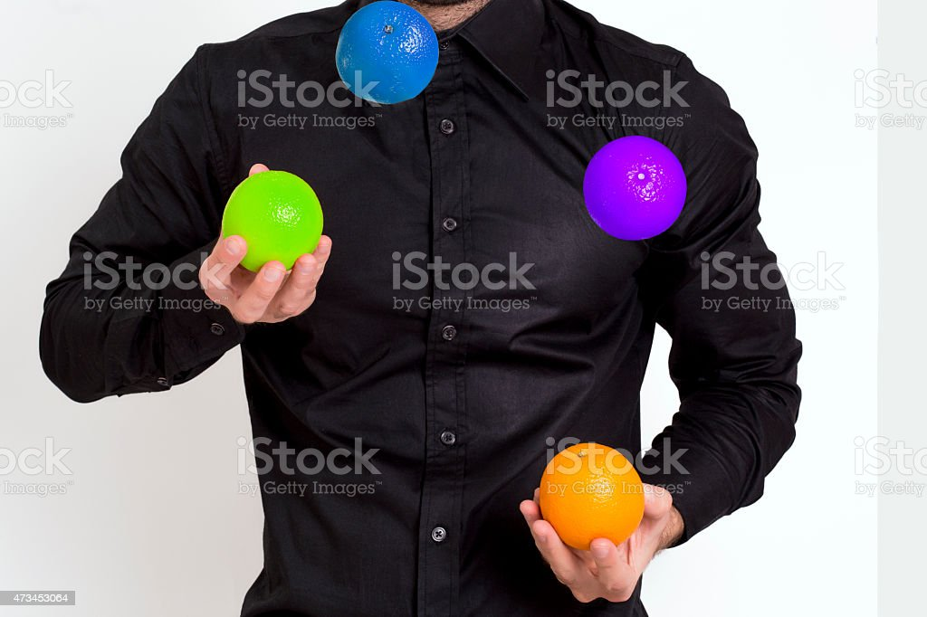 A man juggling with four colored balls stock photo