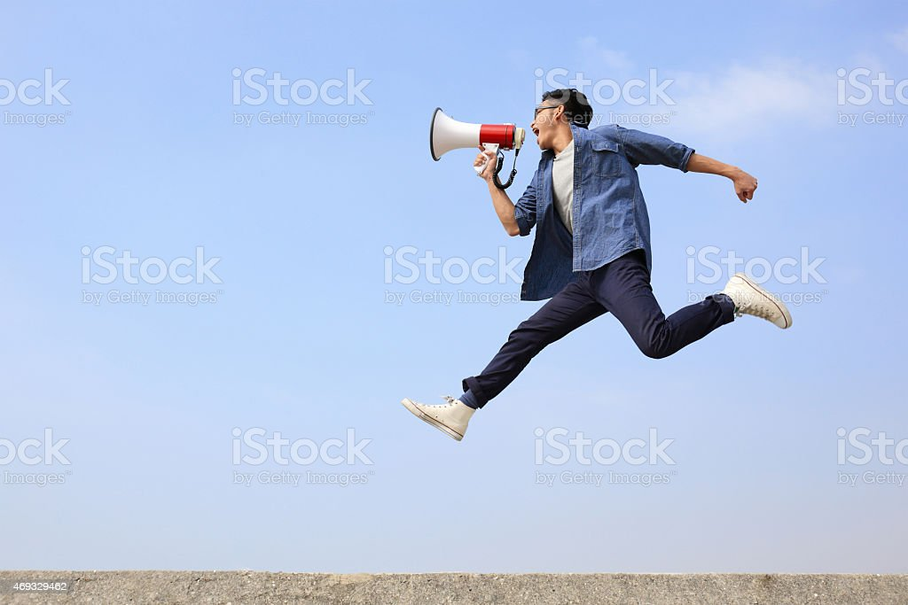 man jump and shout megaphone stock photo