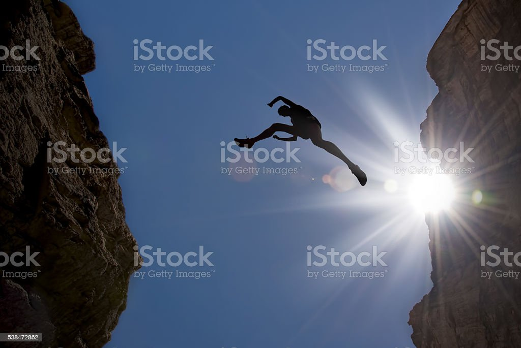 Man Jump through Gap in the Mountain stock photo