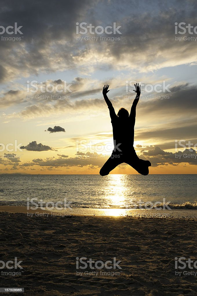 Man Jumping at Sunset by the Sea. royalty-free stock photo