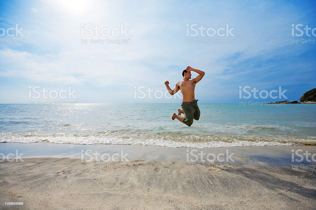 man jumping by the beach happily royalty-free stock photo