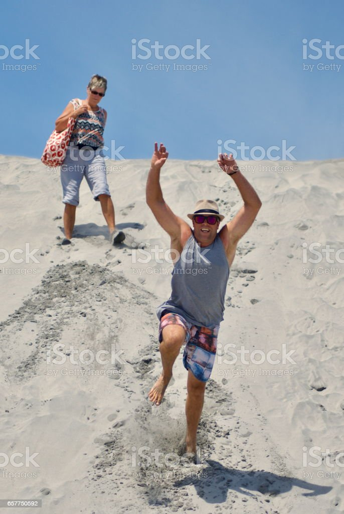 Man jumping down Sand Dune stock photo
