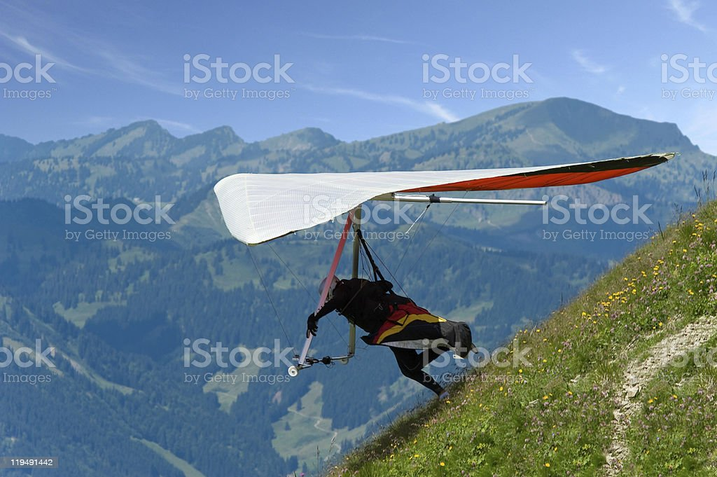 Man jumping from a hill with hang-glider stock photo