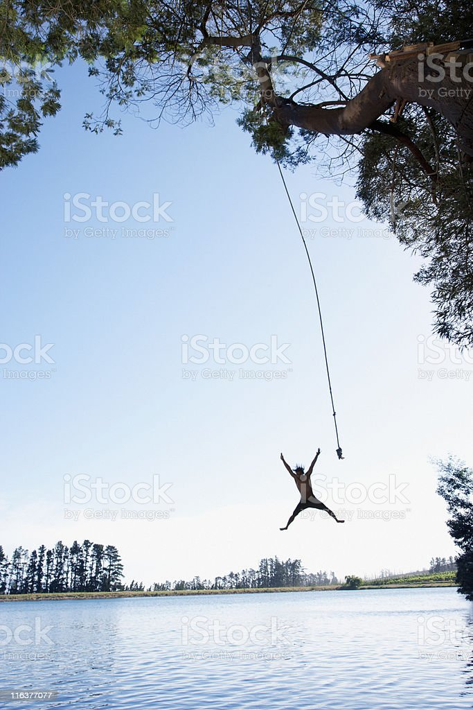 Man jumping from rope swing into lake royalty-free stock photo